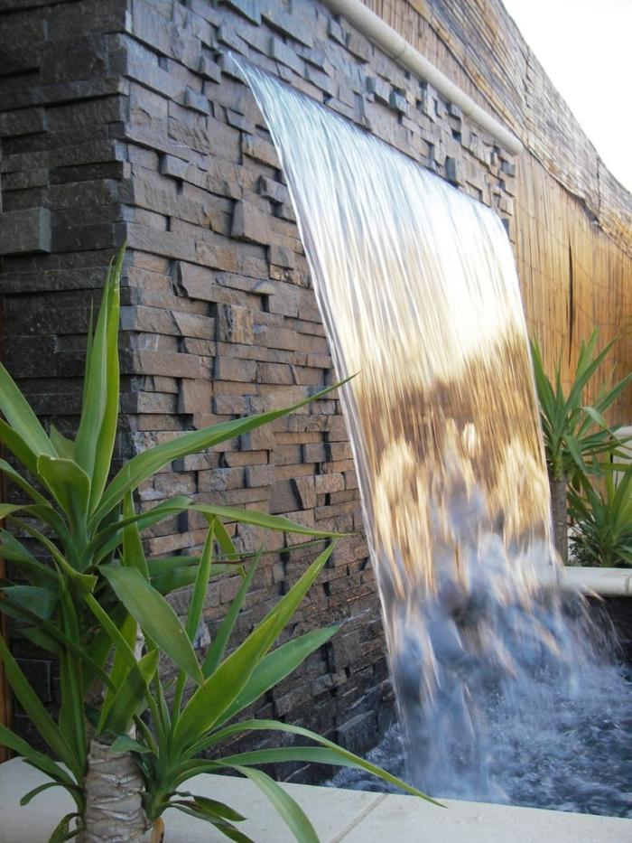 habiller un mur extérieur avec des pierres noires rectangulaires disposées de manière asymétrique, fontaine, jet d'eau de jardin, cascade d'eau avec des plantes vertes des deux cotes