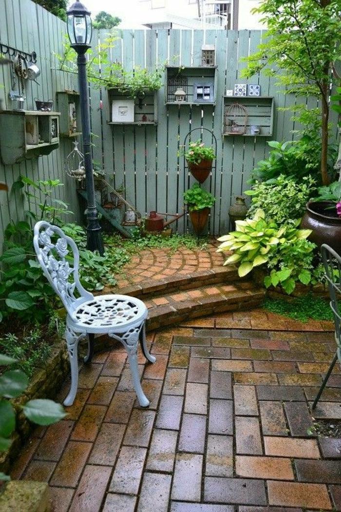 habiller un mur exterieur, aménagement extérieur maison, clôture de bois peint en vert menthe avec des étagères casiers en bois en vert menthe, chaise de jardin style vintage en métal blanc