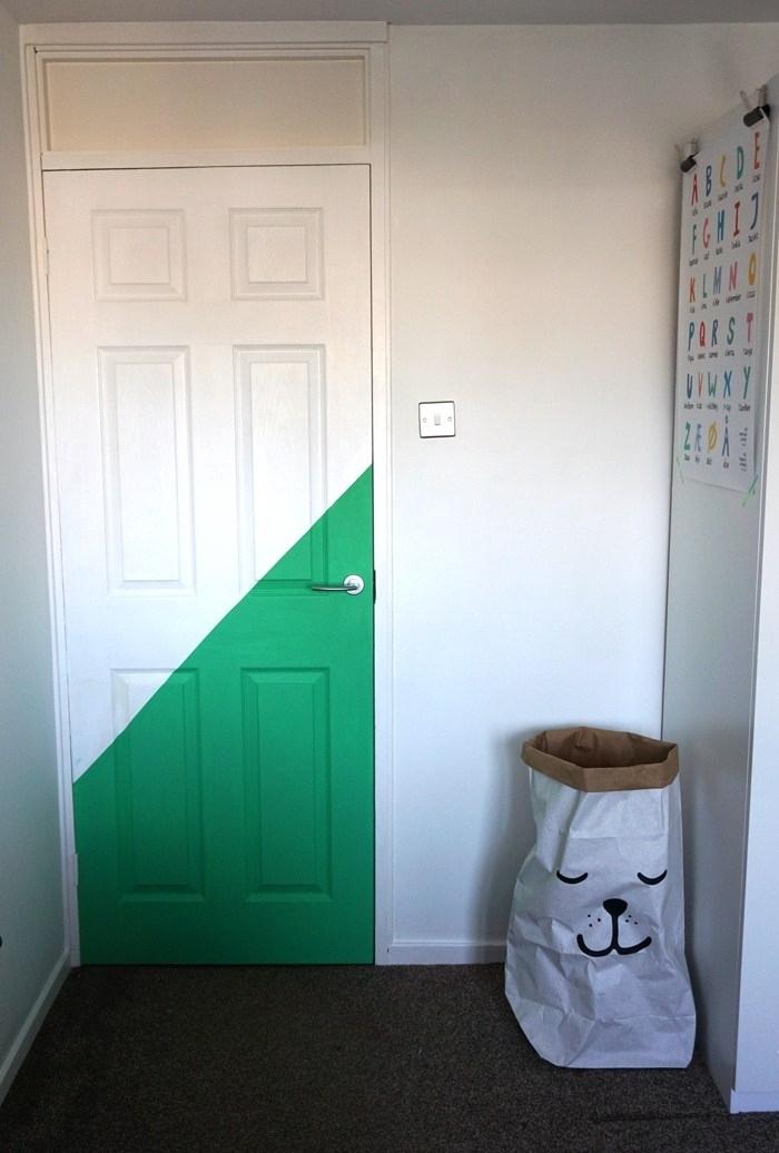 une porte d'intérieur blanche à dessin géométrique en peinture verte qui réveille l'intérieur simplede la chambre d'enfant