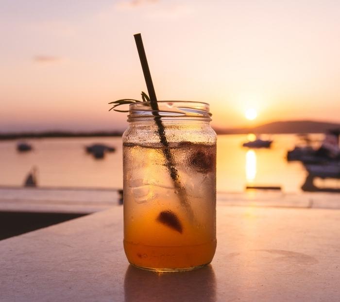 pot de verre rempli d'eau et de glaçon avec jus et tranches de citron, paysage coucher de soleil et boisson froide