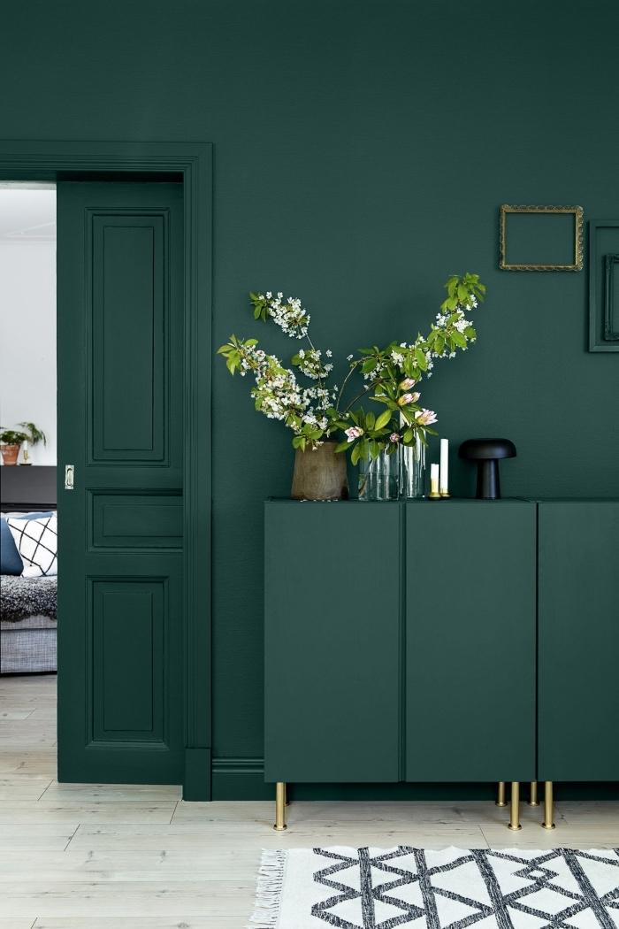 une porte interieure et son encadrement peints de même couleur vert sapin que les murs et la commode, salon design moderne en vert sapin aux accents dorés