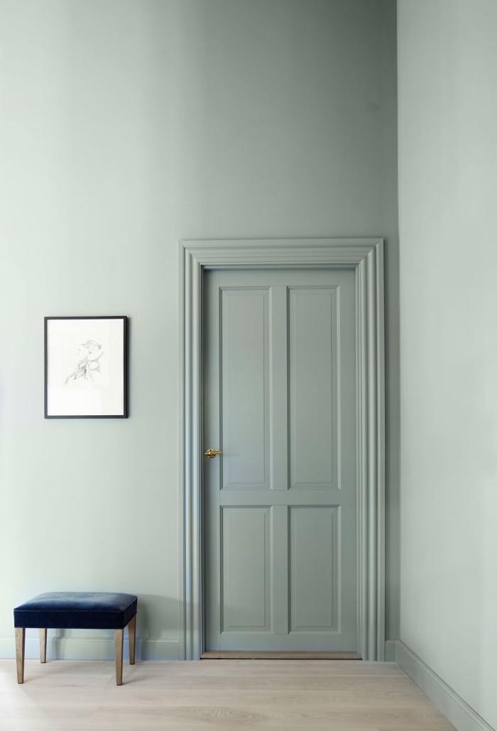une porte interieur bois peint de même couleur vert amande que les murs, qui se fond dans le décor