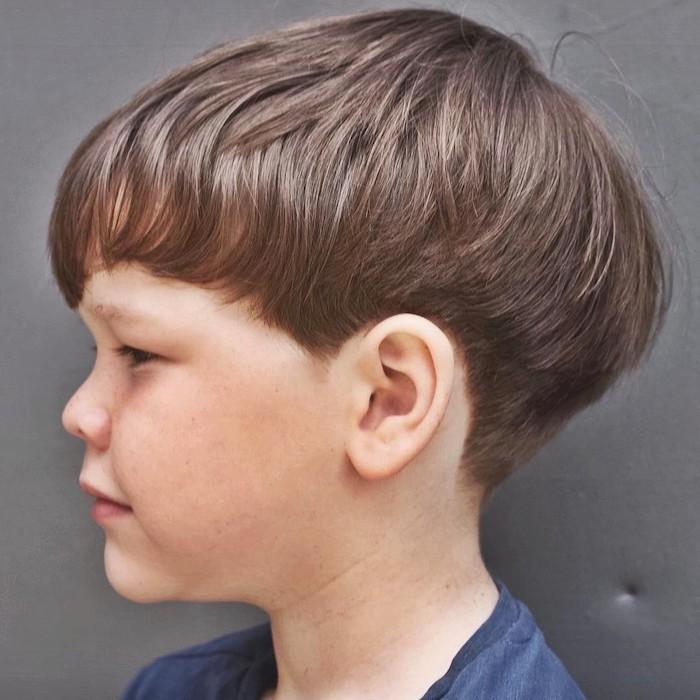 exemple de coupe au bol simple avec des cheveux peignés en avant, frange sur le front, tee shirt bleu marine