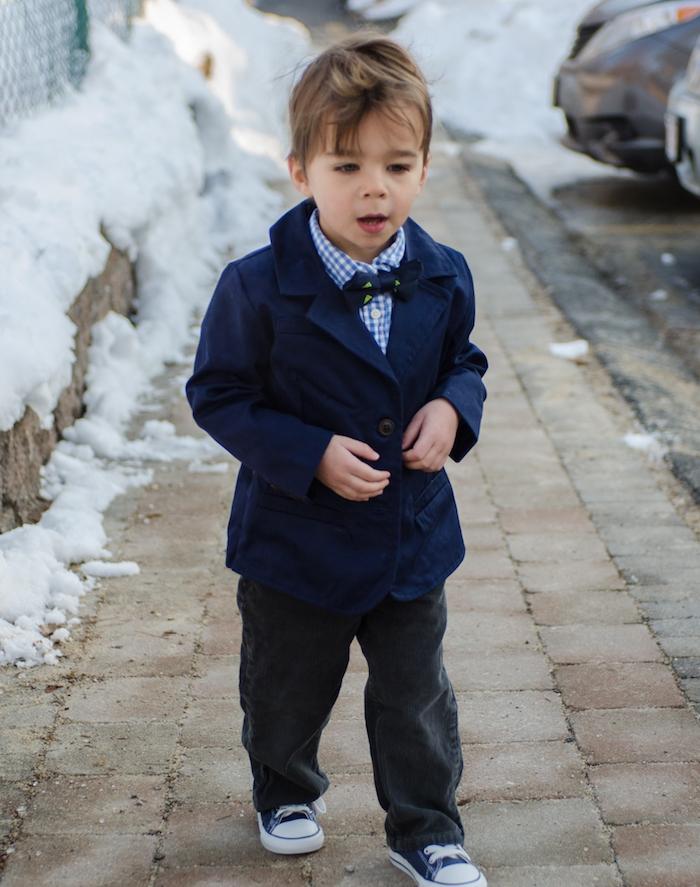 quelle coupe de cheveux pour un petit garçon, une frange longue décoiffée, veste bleu marine, chemise, noeud de papillon