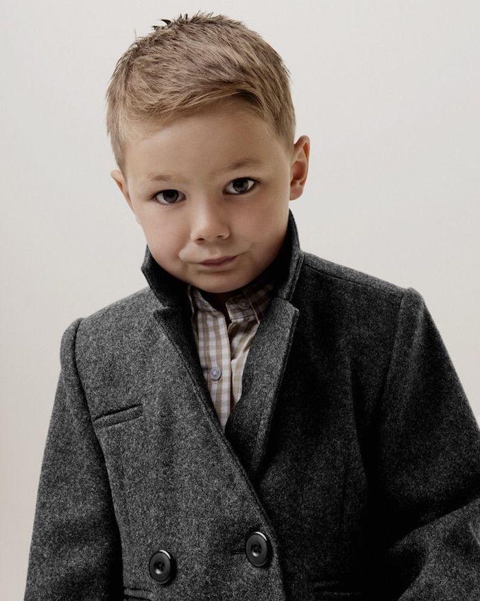 garçon avec une coupe courte, dotée d une frange courte de coté, chemise à carreaux, manteau gris