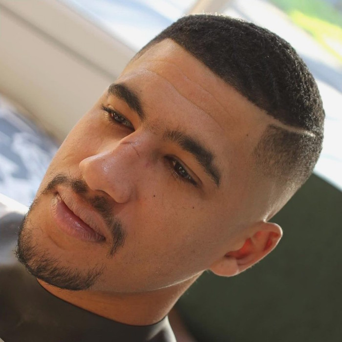 photo de coupe cheveux très court homme métisse afro avec dégradé américain et trait sur le coté