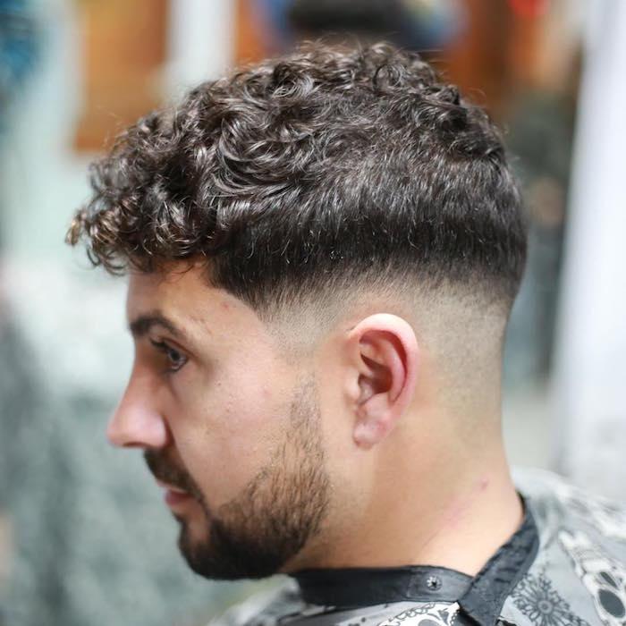 coupe homme rasé coté long dessus avec dégradé arrondi pour cheveux bouclés bruns
