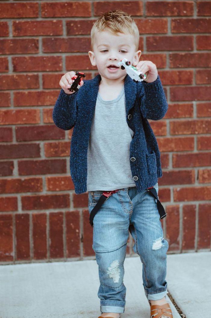 coupe enfant garçon avec un dessus décoiffé plus long et cotés plus courts, jean street style, gilet bleu et débardeur gris