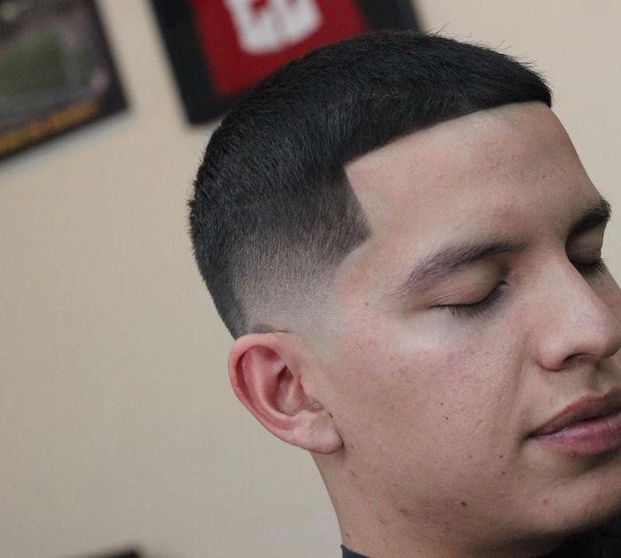 coupe de cheveux homme courte pour cheveux noirs avec dégradé américain et front droit