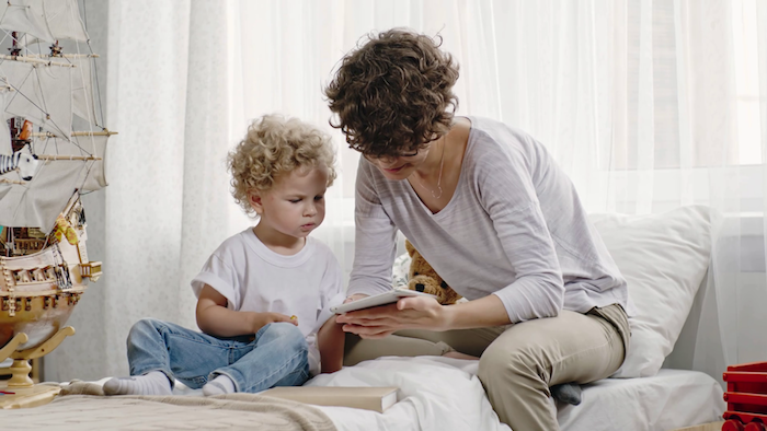 coupe cheveux garcon simple, boucles naturelles laissées pousser, chevelure mi longue ondulée, photo maman et son fils lisent un conte de fée