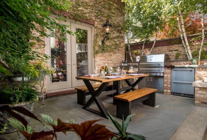 déco de style campagnard dans une cuisine d'été ouverte aménagée avec bancs et table à manger de bois et noir