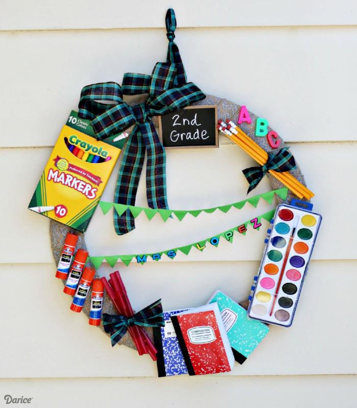 couronne en jute décorée de peinture, carnets, colle, crayons, stylos, lettres alphabet en plastique et ruban à motif carré