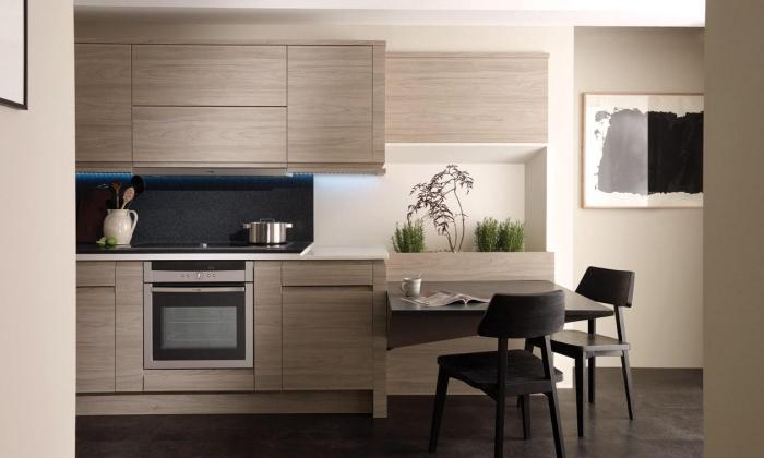 modèle de cuisine tendance aux murs beige et parquet foncé avec meubles de bois gris et crédence noire