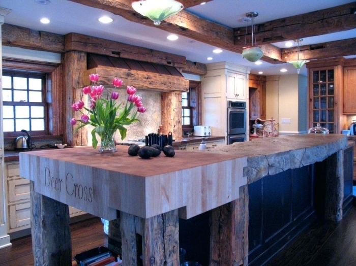 intérieur style rustique dans une cuisine aménagée en bois brut, modèle de plafond blanc avec poutres en bois massif et éclairage led