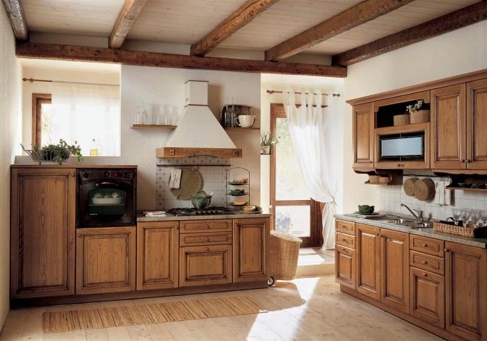 déco d'intérieur rustique dans une cuisine blanche avec plafond en poutres de bois brut et meubles de bois