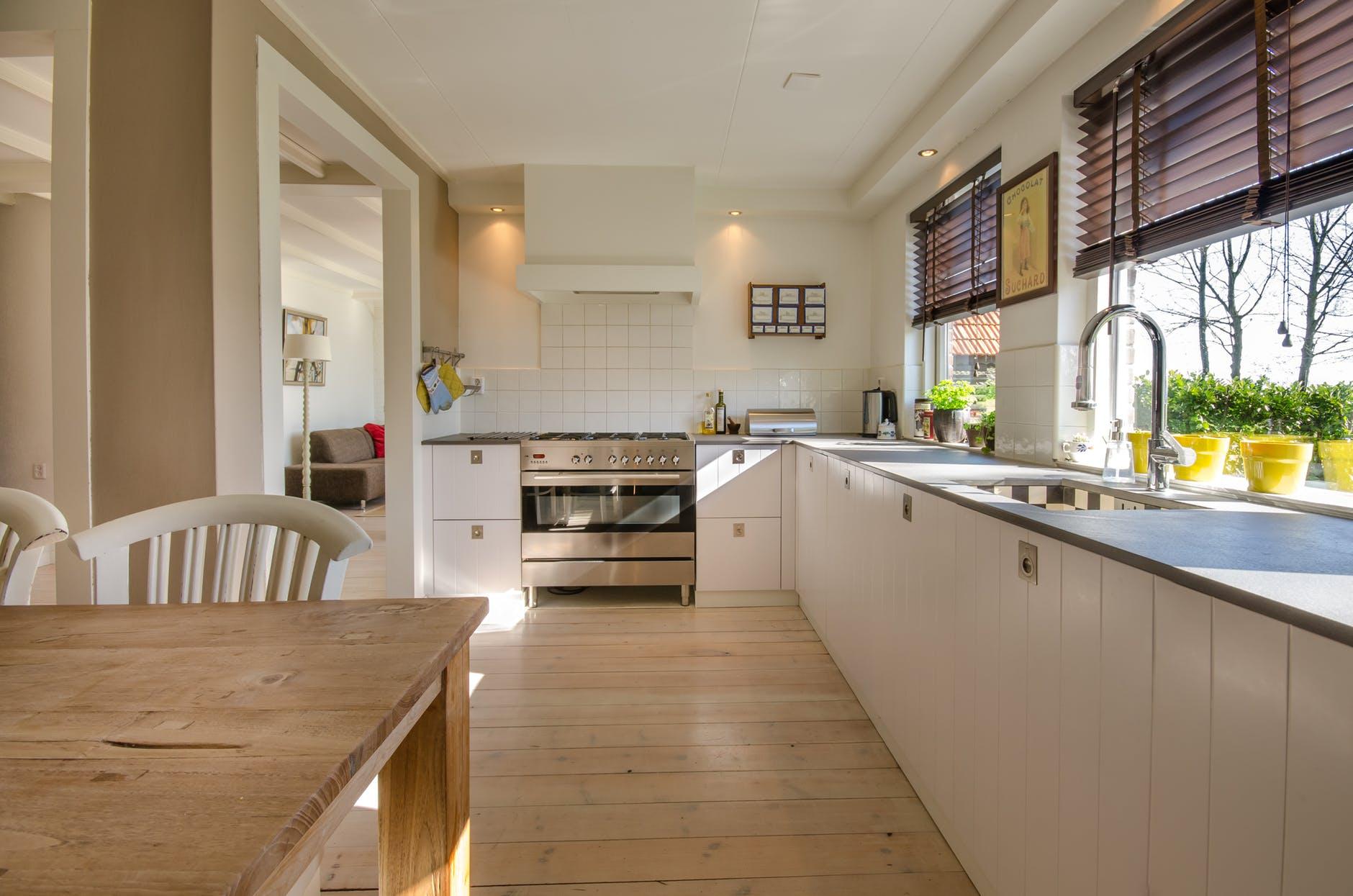 cuisine tendance 2018 avec un meuble bas blanc, table et sol en bois clair, murs blancs, four vintage gris