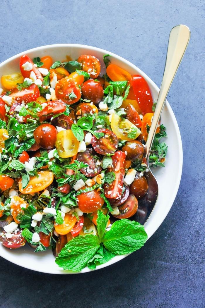 recette méditerranéenne de salade verte composée, de tomates cerises, fromage de feta et d'herbes fraîches comme la menthe, l'origan et le basilic