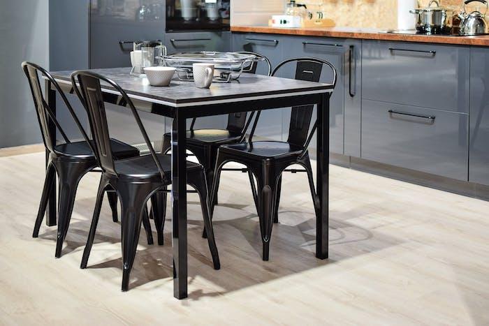 cuisine équipée moderne avec des chaises et table noires et un meuble cuisine gris, doté de plan de travail bois, sol parquet clair
