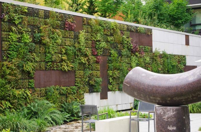 mur vegetal exterieur dans un espace avec des salles d'exposition, motifs carreaux verts, rouges et jaunes, plantes de taille irrégulière