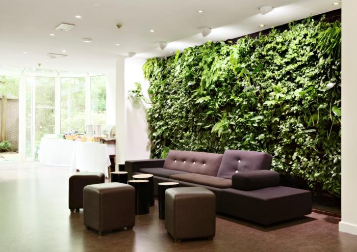 mur végétal intérieur, grand panneau couvrant un grand mur dans un salon aux meubles classiques marrons, sol recouvert de parquet en PVC en marron, plafonniers blancs au plafond