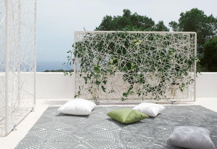mur vegetal exterieur sur un panneau blanc aux fils blancs qui supportent le lierre, installation sur une terrasse avec un grand tapis gris et des coussins en vert, blanc et gris