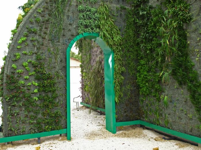 jardin vertical, arc avec la partie intérieure en bois peint en vert herbe, 4 types de plantes vertes qui ornent les murs, parc public, sol recouvert de sable