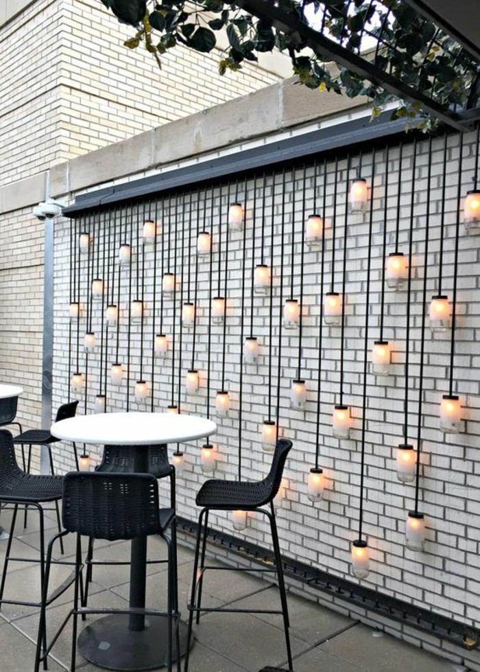idee deco jardin exterieur avec des grandes ampoules suspendues tout au long d'un mur en briques blanches, table haute et ronde avec plan blanc et pieds en métal noir, trois chaises entièrement en noir, en PVC et métal
