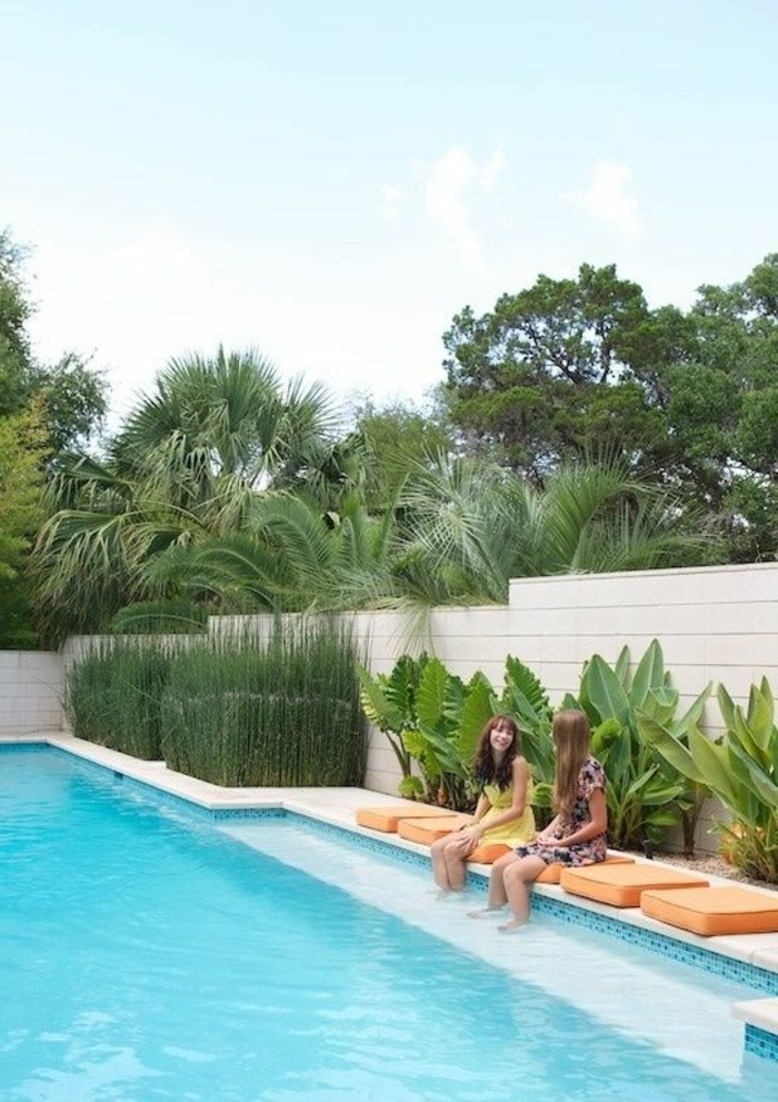 aménagement extérieur maison, idee deco jardin exterieur, habiller un mur extérieur en bois PVC couleur ivoire, grande piscine et coussinets carrés en orange autour de l'eau