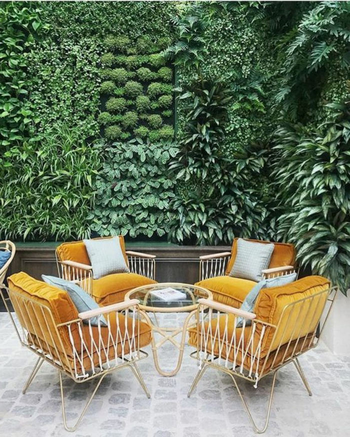 aménagement extérieur maison, décoration murale extérieure, mur vert qui combine plusieurs types de plantes, salon de jardin avec quatre fauteuils aux cadres métalliques blancs avec des coussins en velours orange, petite table ronde avec plan en verre