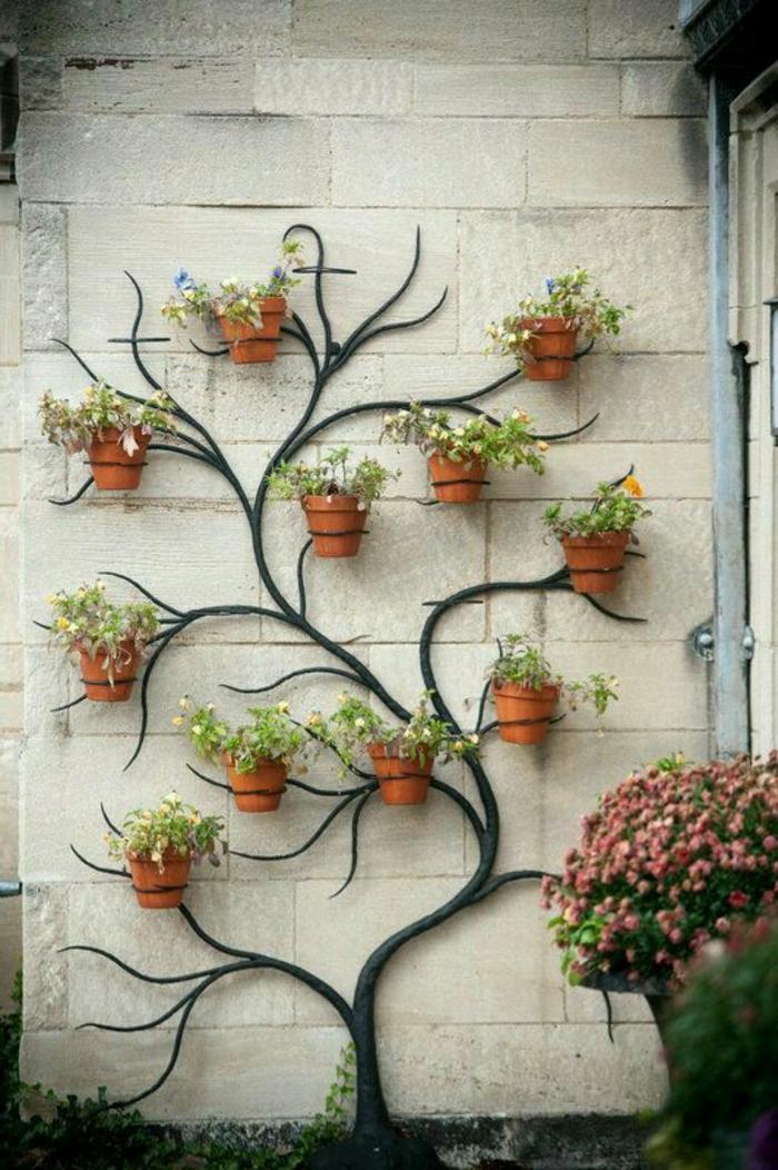 aménagement extérieur maison, mur orné de porte-plante en métal noir en forme d'arbre, avec des branches sur lesquelles on a suspendu des pots avec des fleurs