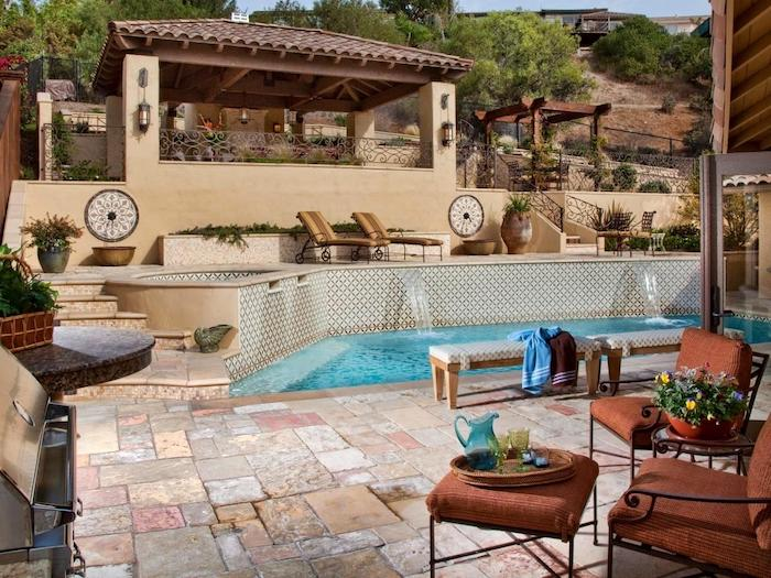 terrasse a l exterieur recouverte de pierres, bancs en bois, chaises et tabourets metalliques, barbecue, bassin d eau, chaise longues sur un coin détente élevé