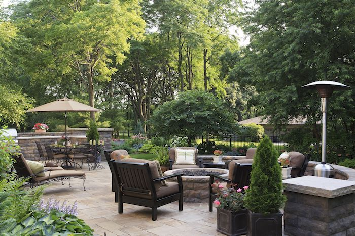 revetement terrasse en dalles de pierre, cheminée extérieure entourée de chaises en bois décorées de coussins marron, chaise longues, coin repas en table et chaise metalliques, plusieurs arbres vertes
