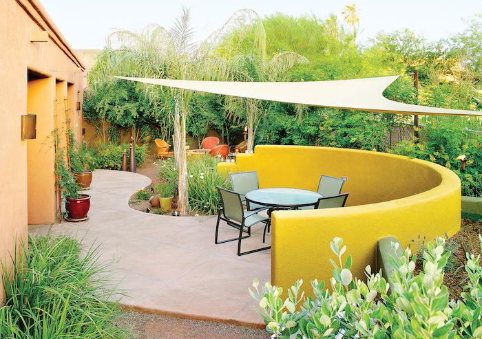 terrasse moderne en dalles de grès cérame avec table ronde et chaises, séparation jaune, plusieurs arbustes, arbres, plantes exotiques, toile d ombrage