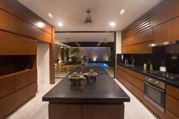 design intérieur cuisine aux murs blancs avec meubles encastrés de bois massif foncé et ilot central en noir et bois brut