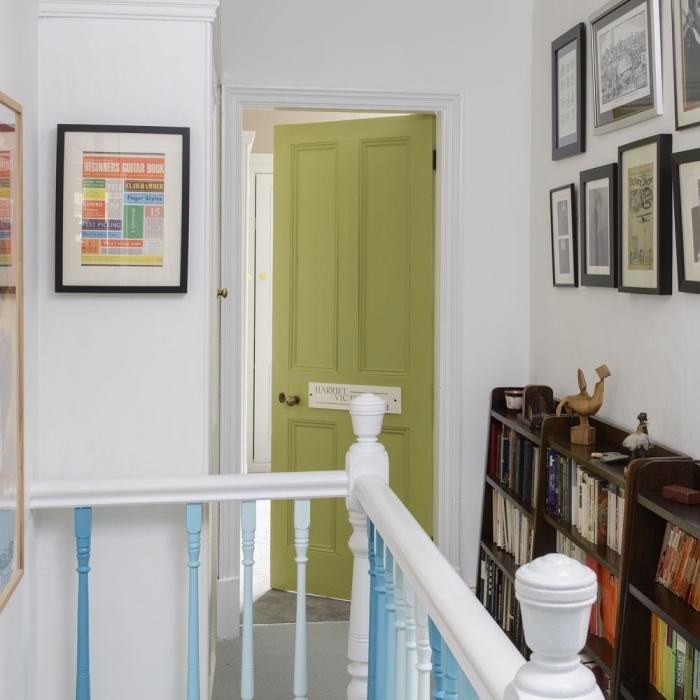 les barreaux d'escalier en dégradés et la porte interieur bois repeinte en vert olive dynamise le couloir blanc