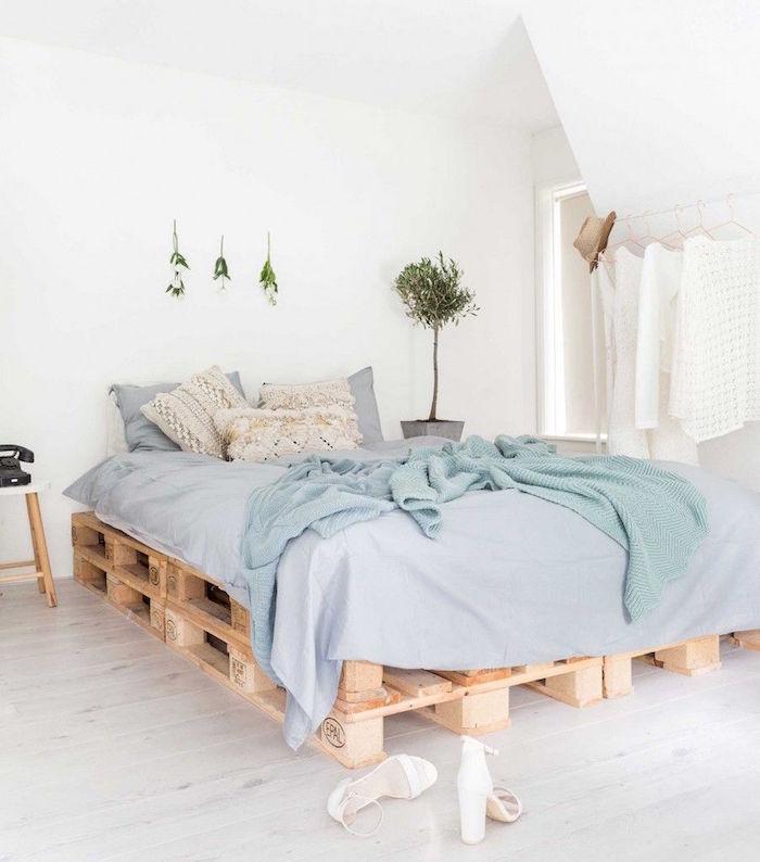 sommier en palette europe double hauteur dans chambre aux murs blancs avec déco minimaliste avec plantes vertes