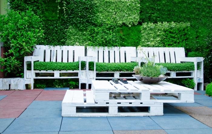 aménagement avec table basse palette et bancs en bois peints en blanc couverts de gazon artificiel vert pour une déco de jardin