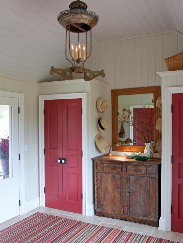entrée rustique avec porte d'intérieur couleur rose sorbet qui s'harmonise avec le tapis à motifs ethniques