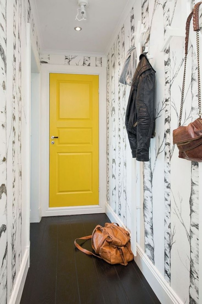 idée originale pour décorer une entrée en jouant sur le contraste de la porte interieur jaune et le revêtement de sol noir, et sur l'originalité du motif du papier peint