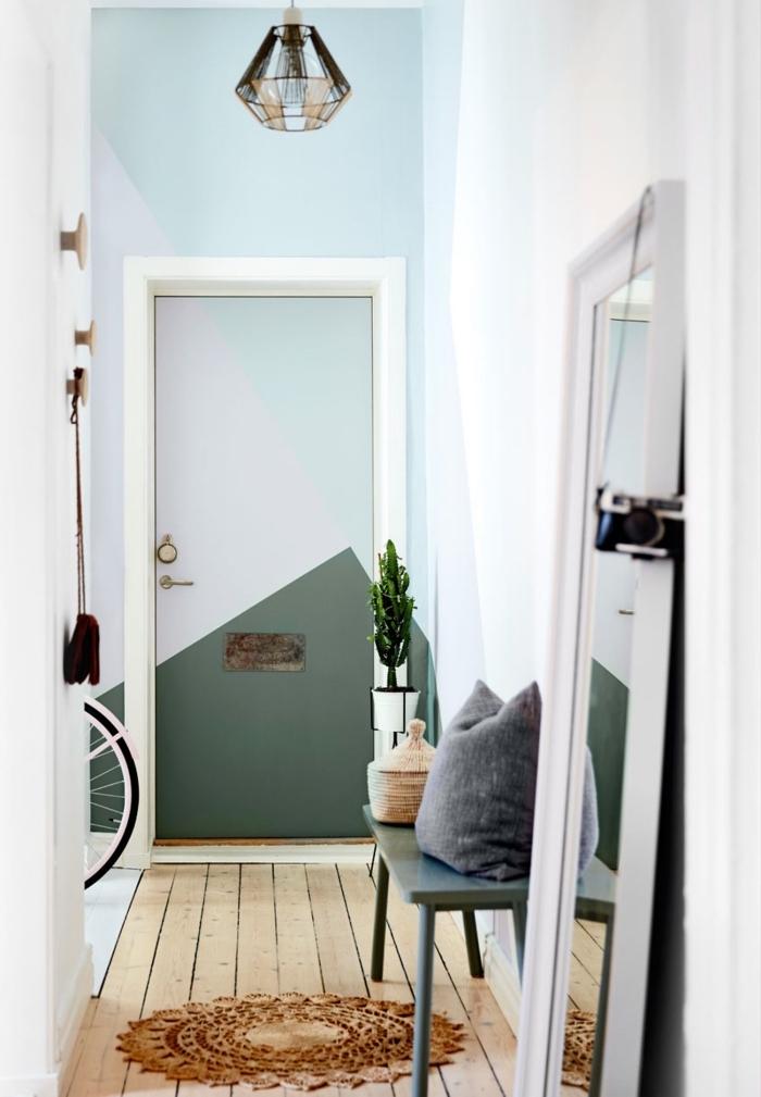 un hall d'entrée scandinave aux accents graphiques avec un mur à motifs géométriques qui se prolongent sur la porte interieure