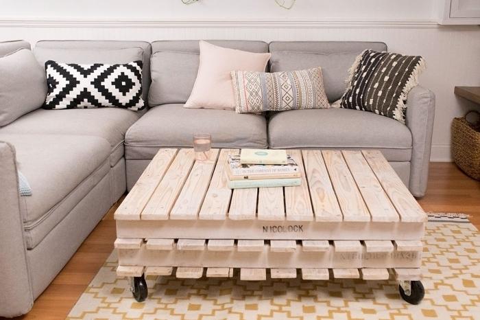 une table basse en palette sur roulettes réalisées avec deux palettes superposées, à l'aspect bois naturel, qui trouvera sa place dans tous
