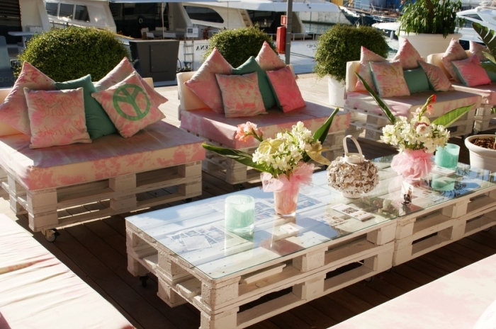 idée quoi faire avec palettes bois, mobilier de jardin avec bancs et table basse en bois et verre décorés de coussins et fleurs