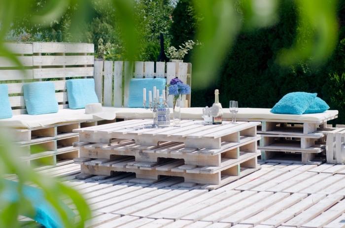 ambiance marine dans un coin extérieur aménagé avec bancs couverts de coussins bleus et table en palette sur un plancher de bois
