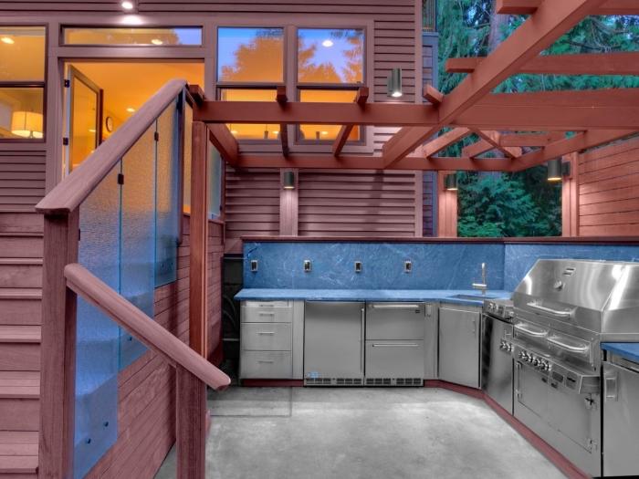 construction de cuisine dans le jardin avec toit en bois et modules en inox et carrelage bleu, modèle de cuisine en L