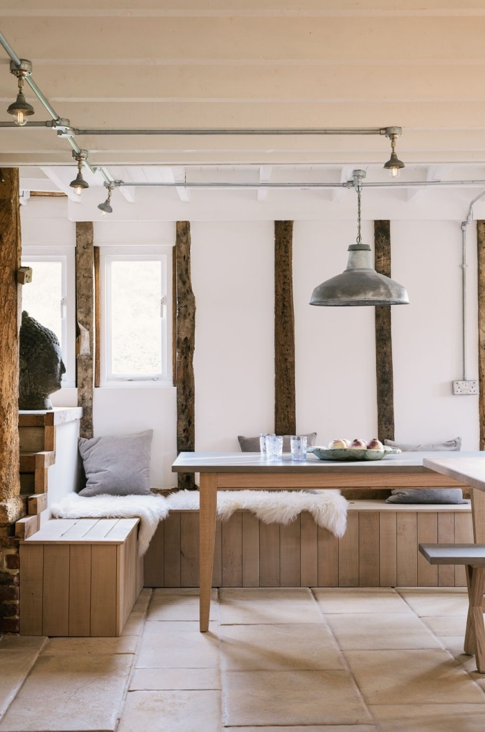 exemple de cuisine blanche et bois aménagée en style cozy avec décoration murale en poutres de bois foncé et carrelage sol beige