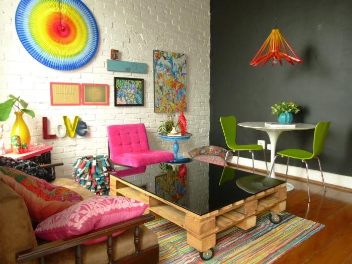 salon éclectique aménagé en style pop art coloré, avec une table basse originale à plateau noir brillant qui s'accorde avec le mur d'accent en ardoise