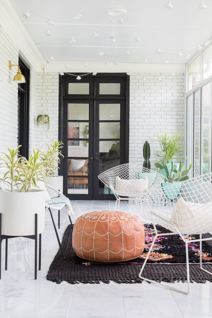 une véranda au style bohème chic qui joue sur les contrastes du blanc et noir, peindre une porte en bois en noir pour la mettre en avant dans un décor dominé par le blanc
