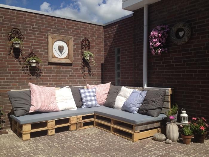 idée pour fabriquer meuble avec palettes de bois couvert de housse siège grise et coussins décoratifs, déco jardin avec canapé d'angle DIY