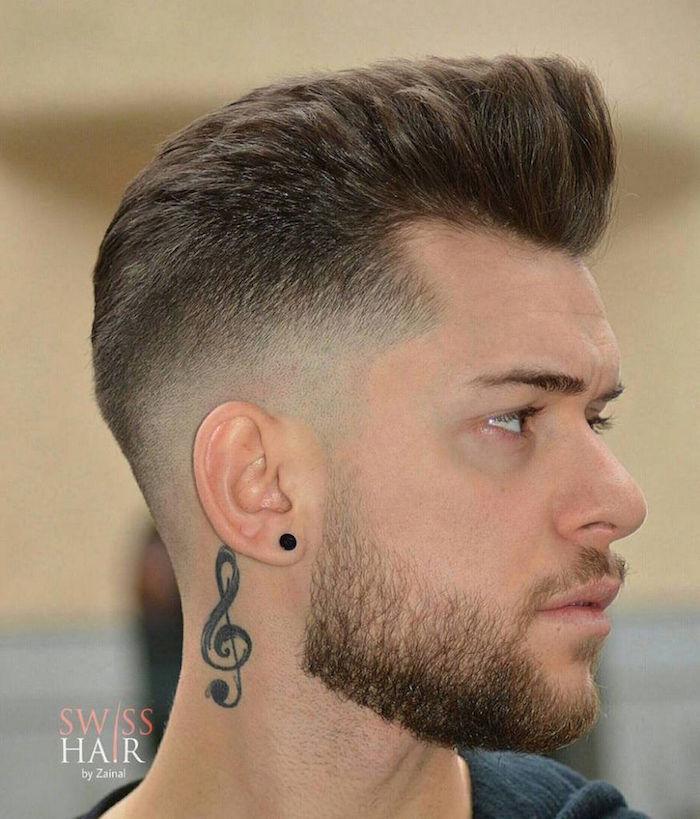 coupe homme mode avec brushing sur le dessus style banane et coté en dégradé et barbe courte et tatouage clef de sol dans le cou