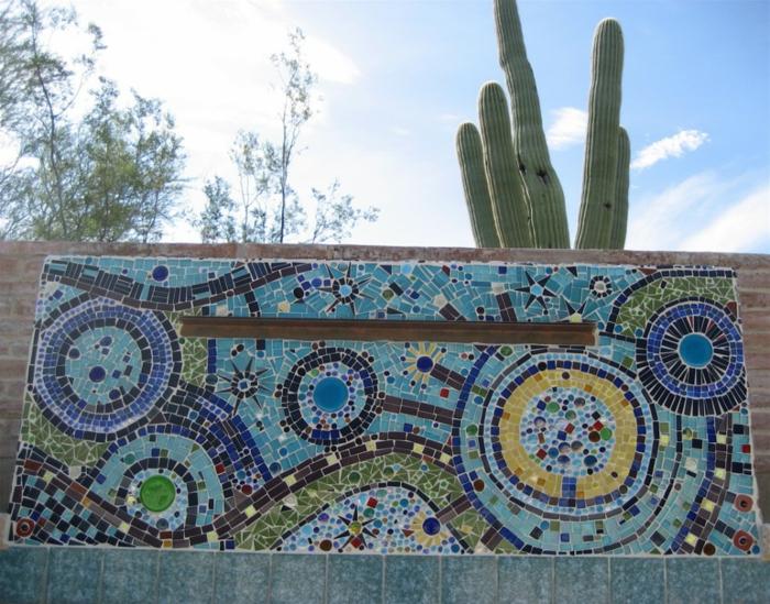 décoration murale extérieure en mosaïque bleu vert et jaune, grand cactus qui s'élève au-dessus de la mosaïque insérée sur un mur en pierres marron clair